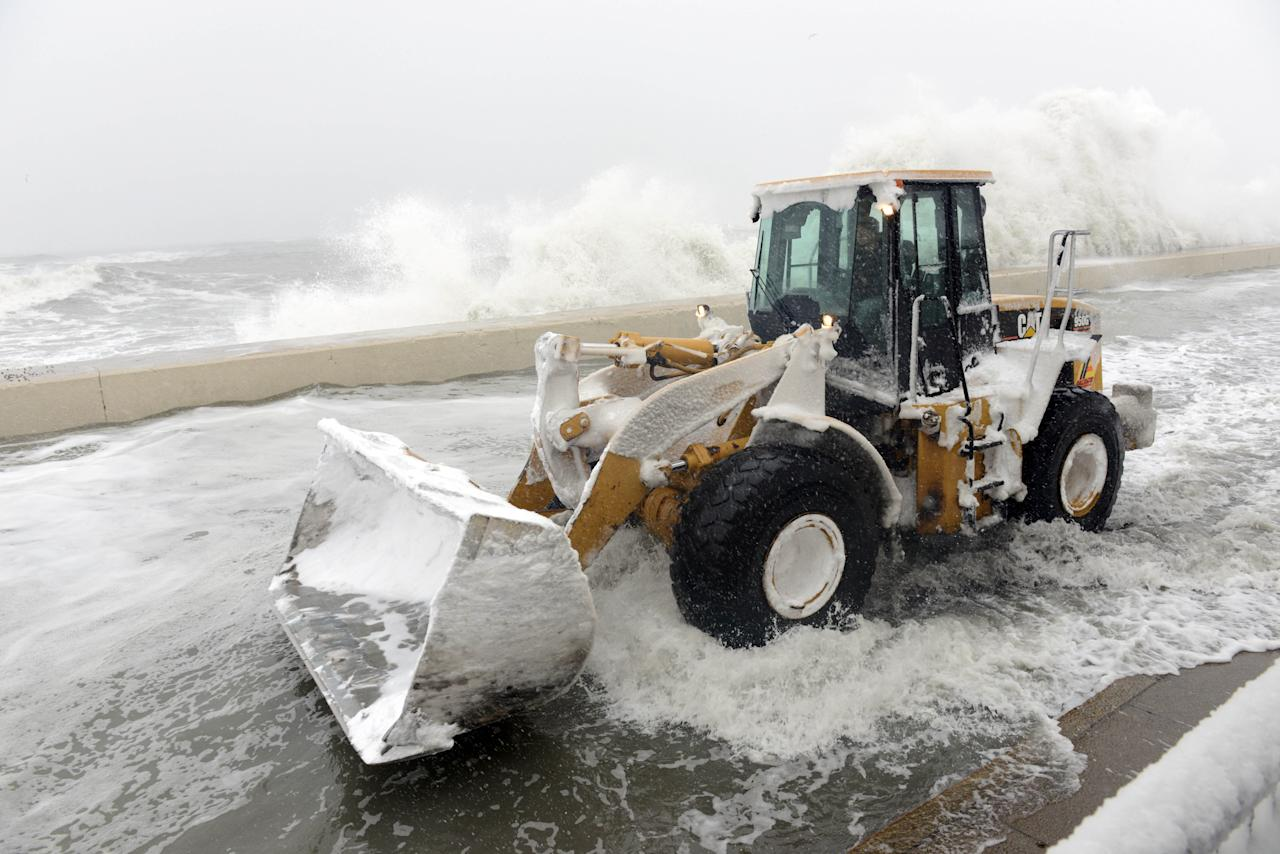 WINTHROP, MA - FEBRUARY 09: A snow plow goes down Winthrop Shore Drive as waves crash over the sea wall February 9, 2013 in Winthrop, Massachusetts. An overnight blizzard left one to two feet of snow in areas, and coastal flooding is expected as the storm lingers into the day. (Photo by Darren McCollester/Getty Images)