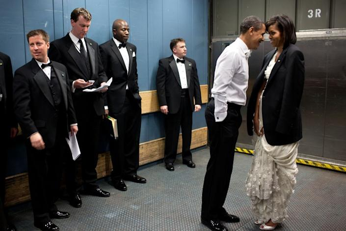 """""""We were on a freight elevator headed to one of the Inaugural balls on Jan. 20, 2009. It was quite chilly, so the President removed his tuxedo jacket and put it over the shoulders of his wife. Then they had a semi-private moment as staff members and Secret Service agents tried not to look."""" (Pete Souza / The White House) <br> <br> <a href=""""http://lightbox.time.com/2012/10/08/pete-souza-portrait-of-a-presidency/#1"""" rel=""""nofollow noopener"""" target=""""_blank"""" data-ylk=""""slk:Click here to see the full collection at TIME.com"""" class=""""link rapid-noclick-resp"""">Click here to see the full collection at TIME.com</a>"""