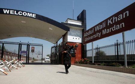 A policeman gestures as he stands guard at the entry of Abdul Wali Khan University where Mashal Khan, accused of blasphemy, was killed by a mob, in Mardan