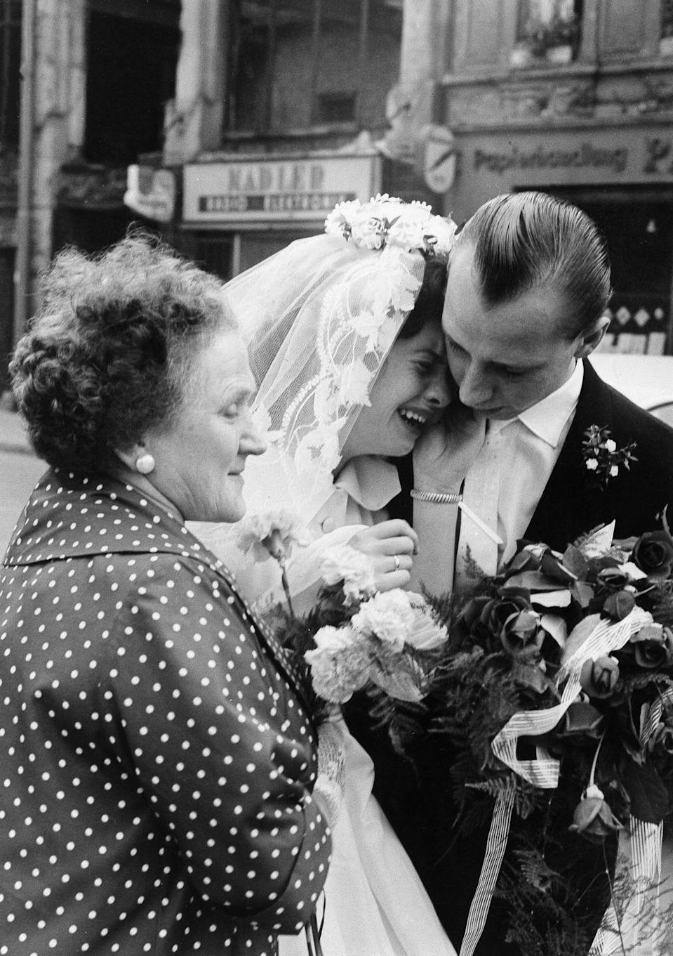 <p>The Berlin Wall was built in 1961, effectively dividing the German city in half. This photo, taken during the first year of the wall's existence, shows the bride with her parents, who resided in East Berlin and were unable to get permission to take part in their daughter's wedding in West Berlin.</p>