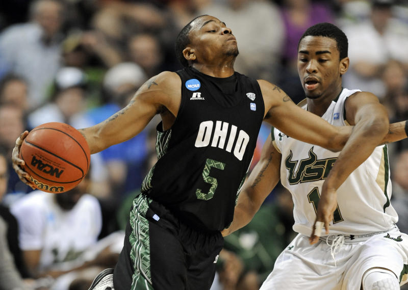Ohio guard D.J. Cooper (5) gets tangled with South Florida guard Anthony Collins (11) in the first half of a third-round NCAA men's college basketball tournament game Sunday, March 18, 2012, in Nashville, Tenn. (AP Photo/Donn Jones)