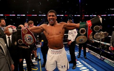 Anthony Joshua celebrates with the IBF, WBA Super, WBO & IBO World Heavyweight belts - Credit: Richard Heathcote/Getty Images