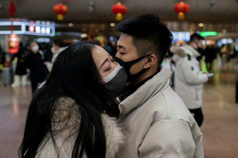 A virus-free adieu: this couple at the at Beijing West Railway Station takes extra precautions as they travel for the Lunar New Year holiday (AFP Photo/NICOLAS ASFOURI)