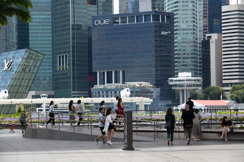 This photograph taken on February 18, 2020 shows people walking near commercial buildings in the central business district in Singapore. - Singapore's economy, a bellwether for trade-reliant Asian countries, suffered its worst contraction since the global financial crisis in the first quarter as the coronavirus pandemic escalated, official data showed on March 26. (Photo by ROSLAN RAHMAN / AFP) (Photo by ROSLAN RAHMAN/AFP via Getty Images)