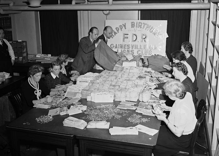 Staff sift through mail and makes piles of dimes in the 1940s.