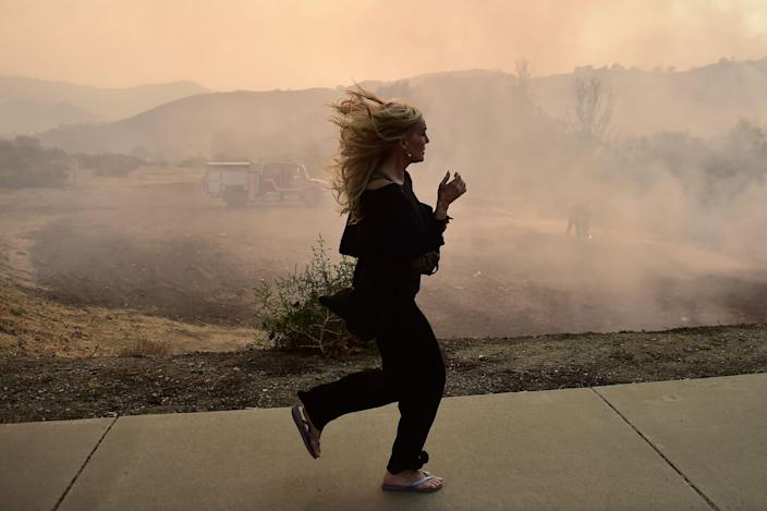 <p>A woman runs as firefighters work to control a flare up due to flying embers from the Woolsey Fire, Nov. 10, 2018 in Calabasas, Calif. (Photo: Robyn Beck / AFP/Getty Images) </p>