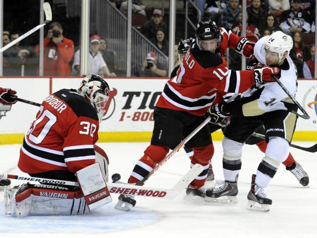 New Jersey Devils goaltender Martin Brodeur, left, makes a save on a shot by Pittsburgh Penguins' Chris Kunitz, right, as he is checked by Devils Peter Harrold during the first period of an NHL hockey game Saturday, Nov. 16, 2013, in Newark, N.J. (AP Photo/Bill Kostroun)