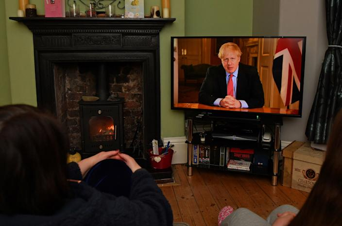 """TOPSHOT - Members of a family listen as Britain's Prime Minister Boris Johnson makes a televised address to the nation from inside 10 Downing Street in London, with the latest instructions to stay at home to help contain the Covid-19 pandemic, from a house in Liverpool, north west England on March 23, 2020. - Britain on Monday ordered a three-week lockdown to tackle the spread of coronavirus, shutting """"non-essential"""" shops and services, and banning gatherings of more than two people. """"Stay at home,"""" Prime Minister Boris Johnson said in a televised address to the nation, as he unveiled unprecedented peacetime measures after the death toll climbed to 335. (Photo by Paul ELLIS / AFP) (Photo by PAUL ELLIS/AFP via Getty Images)"""