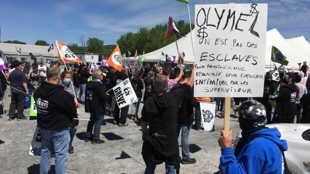 A striking worker outside an Olymel meat plant in Quebec's Beauce region holds a sign that says, 'We are not slaves.' Workers decry bad working conditions and low salaries in the strike that has lasted more than two months. (Sebastien Vachon/Radio-Canada - image credit)
