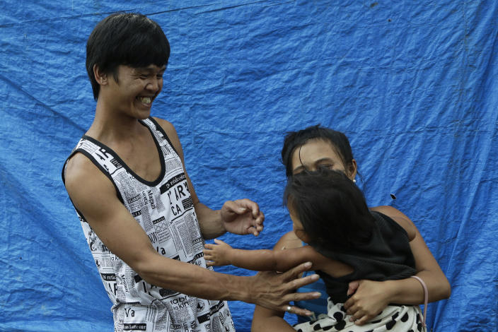 Ronnel Manjares, left, and Trisha May Noche, right, play with their daughter Crystal outside the house of their relative in Tanauan, Batangas province, Philippines, Wednesday, July 15, 2020. Their 16-day-old son Kobe was heralded as the country's youngest COVID-19 survivor. But the relief and joy proved didn't last. Three days later, Kobe died on June 4 from complications of Hirschsprung disease, a rare birth defect. (AP Photo/Aaron Favila)