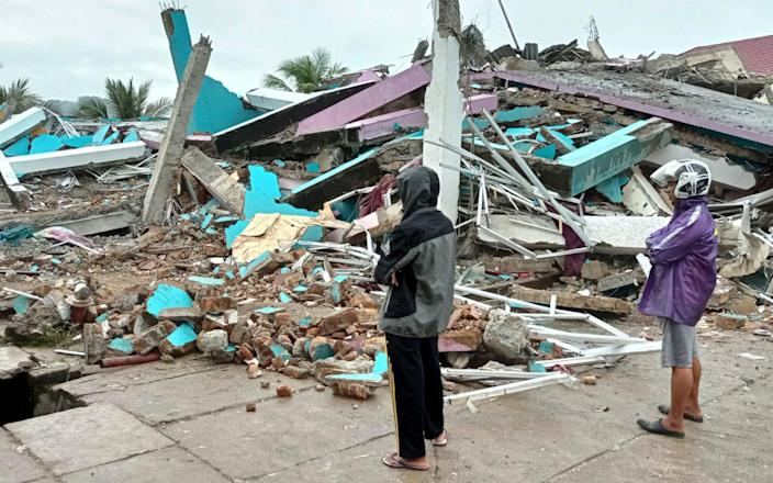 People look at a damaged hospital building following an earthquake in Mamuju, West Sulawesi province - Reuters