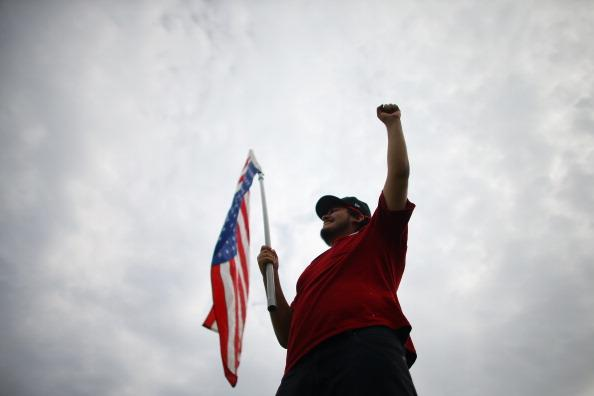 Thomas Bolanos holds an American flag as he joins others in a protest in front of a Raytheon company building which they say is building military drones on August 23, 2012 in Largo, Florida. The protest is one of many planned by activists who want to state their views on the economy or other issues before and during the Republican National Convention in Tampa, Florida during the week of August 27th. (Photo by Joe Raedle/Getty Images)