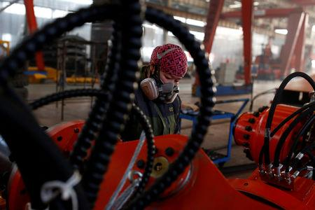 A woman works in the Tianye Tolian Heavy Industry Co. factory in Qinhuangdao in the QHD economic development zone, Hebei province, China December 2, 2016.   REUTERS/Thomas Peter/File Photo                  GLOBAL BUSINESS WEEK AHEAD PACKAGE       SEARCH BUSINESS WEEK AHEAD 12 DEC FOR ALL IMAGES