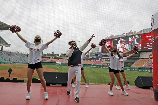 FILE - In this May 5, 2020, file photo, SK Wyverns' cheerleaders cheer for their team during a baseball game against Hanwha Eagles in Incheon, South Korea. Take a look across the globe and mascots remained a staple of baseball games in Taiwan and the KBO League in South Korea. The cheerleaders provide a soundtrack for an otherwise dreary atmosphere. (AP Photo/Lee Jin-man, File)