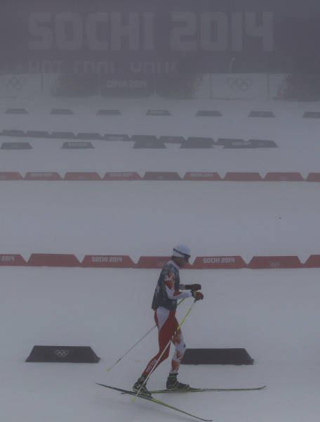 Unidentified athletes ski through the fog as the men's biathlon 15K mass start race has been postponed due to the lack of visibility at the 2014 Winter Olympics, Sunday, Feb. 16, 2014, in Krasnaya Polyana, Russia. (AP Photo/Gregorio Borgia)