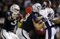 Oakland Raiders tackle Jared Veldheer blocks Denver Broncos defensive tackle Mitch Unrein, right, as Raiders quarterback Carson Palmer (3) loses control of the ball during the third quarter of an NFL football game in Oakland, Calif., Thursday, Dec. 6, 2012. (AP Photo/Marcio Jose Sanchez)