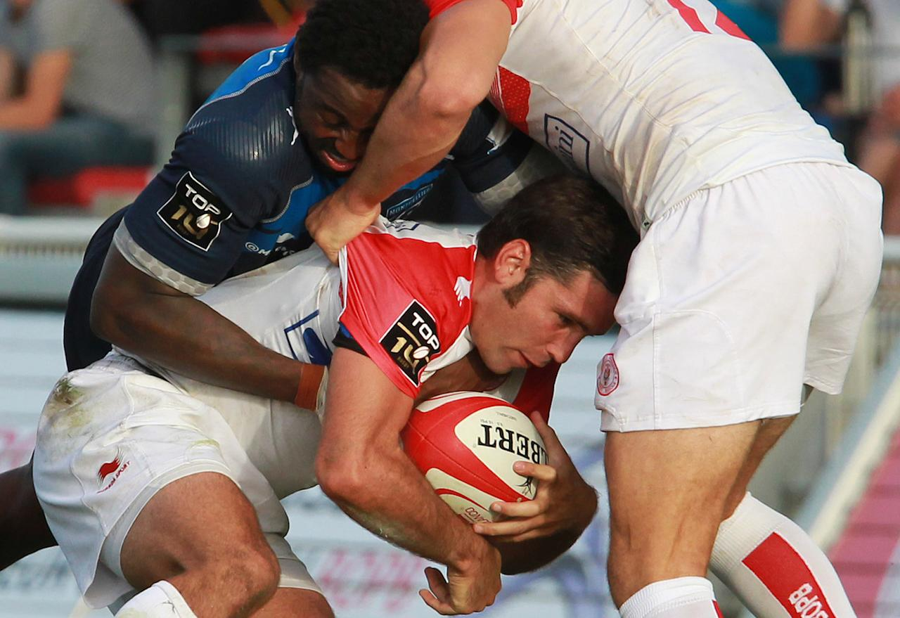 Biarrritz's Dimitri Yachvili, center, is tackled by Montpellier's Fulgence Ouedraogo, left, during their French Top 14 rugby union match at the Stade Aguilera, in Biarritz, southwestern France, Saturday Aug. 24, 2013. (AP Photo/Bob Edme)
