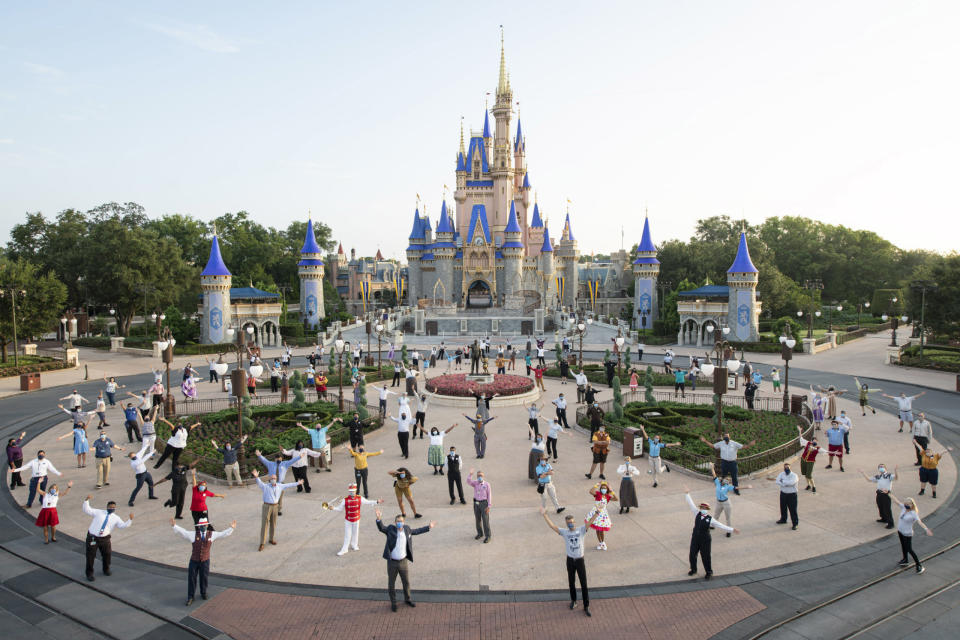"Disney cast members appear in front of Magic Kingdom Park ahead of its reopening on Saturday. Experts say the decision to resume business is ""irresponsible"" and dangerous. (Photo by David Roark/Walt Disney World Resort via Getty Images)"