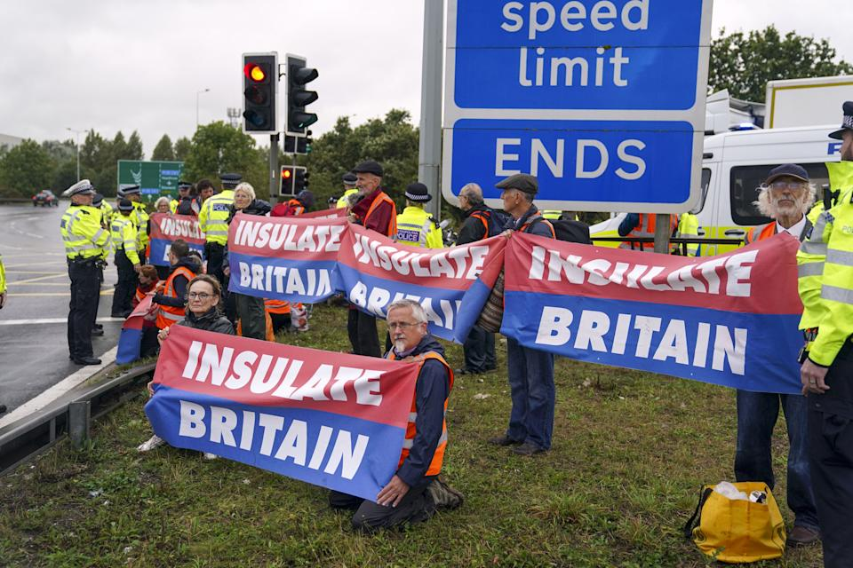 Members of Insulate Britain occupying a roundabout leading from the M25 motorway to Heathrow Airport in London. Picture date: Monday September 27, 2021.