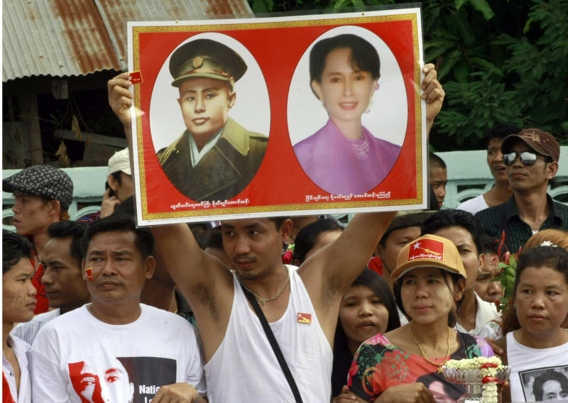 A Myanmar migrant worker holds a portrait of Myanmar's opposition leader Aung San Suu Kyi with her father General Aung San while waiting for the arrival of Aung San Suu Kyi outside the airport in Mae Sot town near the Thai-Myanmar border Saturday, June 2, 2012. Suu Kyi turned her attention to Myanmar's long-standing refugee crisis Saturday with a visit to a sprawling camp on Thailand's border to get her first glimpse of the hardships faced by hundreds of thousands who have fled war in her homeland. (AP Photo/Apichrt Weerawong)