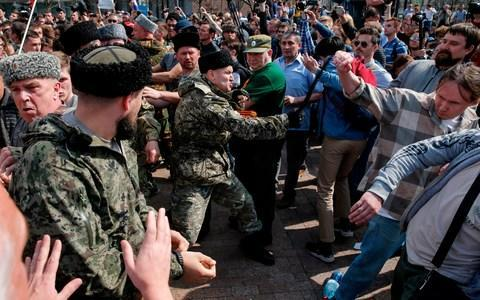 <span>A Cossack whips opposition protesters in Moscow in May</span> <span>Credit: Maxim Zmeyev/AFP </span>