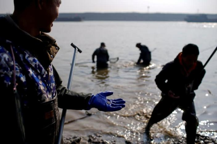 FILE PHOTO: A fisherman holds a copper coin found in debris by a dwindling river that feeds the Poyang lake, China