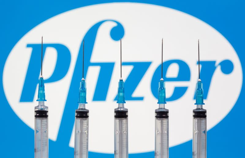 Syringes are seen in front of a displayed Pfizer logo in this illustration