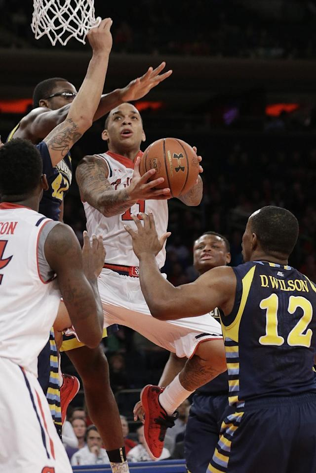 St. John's' D'Angelo Harrison (11) drives past Marquette's Chris Otule (42) and Derrick Wilson (12) during the second half of an NCAA collage basketball game Saturday, Feb. 1, 2014, in New York. (AP Photo/Frank Franklin II)