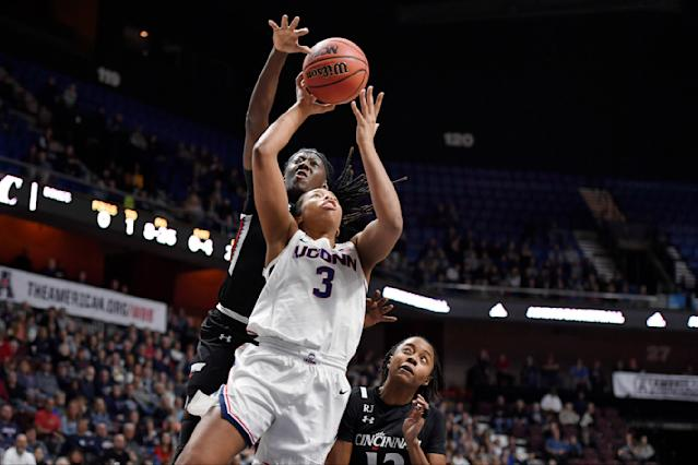 Connecticut's Megan Walker (3) goes up for a basket as Cincinnati's Florence Sifa, back, and Cincinnati's Antoinette Miller, right, defend during the first half of an NCAA college basketball game in the American Athletic Conference tournament finals at Mohegan Sun Arena, Monday, March 9, 2020, in Uncasville, Conn. (AP Photo/Jessica Hill)