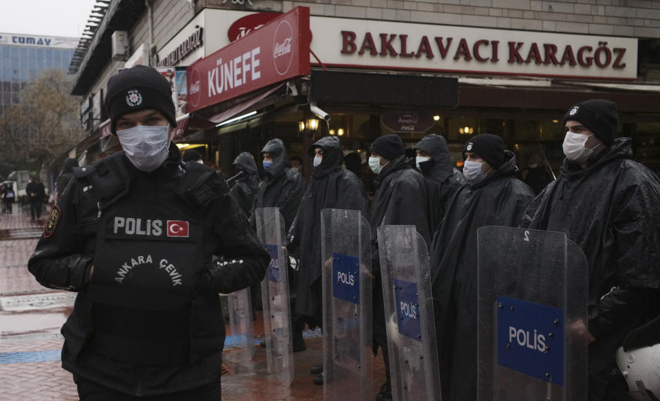 """Riot police officers wearing masks to protect against the spread of coronavirus, stand in the rain during a women's right protest, in Ankara, Turkey, Saturday, March 20, 2021. Turkey's weekly geographic COVID-19 figures keep increasing according to Health ministry statistics released late Saturday as the country continues its """"controlled normalization."""" (AP Photo/Burhan Ozbilici)"""