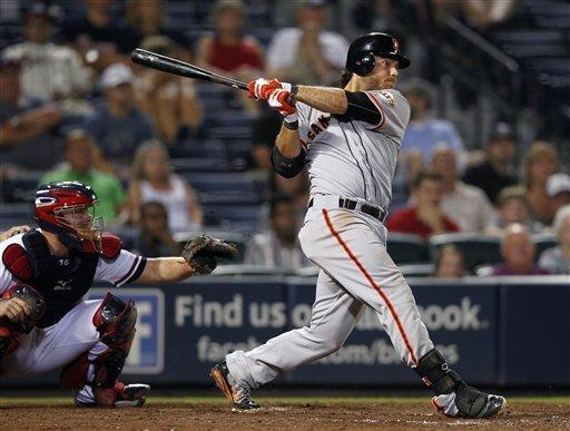 San Francisco Giants' Brandon Crawford (35) follows through with a three-run home run as Atlanta Braves catcher Brian McCann (16) looks on in the 11th inning of a baseball game Wednesday, July 18, 2012 in Atlanta. San Francisco Giants won 9-4 in 11 innings. (AP Photo/John bazemore)