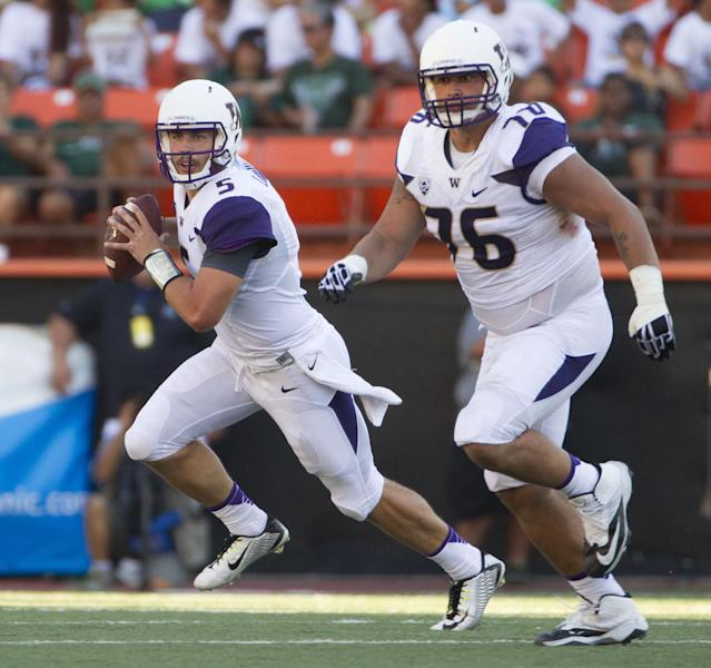 Washington quarterback Jeff Lindquist (5) rolls out to pass while being protected by offensive linesman Dexter Charles (76) in the second quarter of an NCAA college football game against Hawaii, Saturday, Aug. 30, 2014, in Honolulu. (AP Photo/Eugene Tanner)