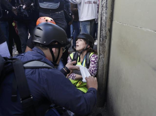 A journalist working for CNN receives medical attention after being injured in clashes between demostrators and mlitary police during a protest against the 2014 World Cup, in Sao Paulo June 12, 2014. REUTERS/Ricardo Moraes (BRAZIL - Tags: SPORT SOCCER WORLD CUP POLITICS CIVIL UNREST MEDIA)
