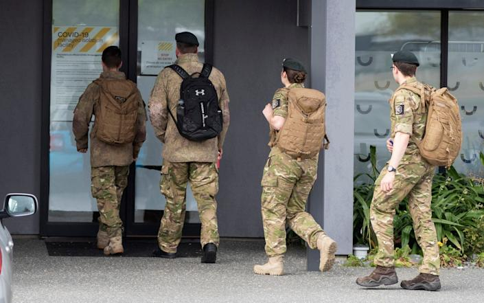 Military personnel arrive at the hotel where crew members have been in quarantine - AP