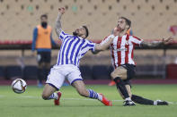 Athletic Bilbao's Inigo Martinez, right, fouls Real Sociedad's Portu, in the penalty box during the final of the 2020 Copa del Rey, or King's Cup, soccer match between Athletic Bilbao and Real Sociedad at Estadio de La Cartuja in Sevilla, Spain, Saturday April 3, 2021. The game is the rescheduled final of the 2019-2020 competition which was originally postponed due to the coronavirus pandemic. (AP Photo/Angel Fernandez)
