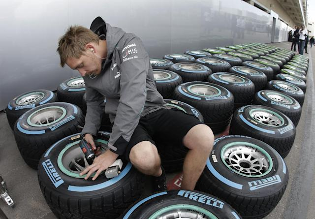 McLaren crew member works on tires in preparation for the Formula One U.S. Grand Prix auto race at the Circuit of the Americas, Thursday, Nov. 14, 2013, in Austin, Texas. (AP Photo/Darron Cummings)