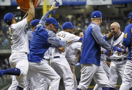 May 25, 2018; Milwaukee, WI, USA; Milwaukee Brewers third baseman Travis Shaw (21) celebrates with teammates after drawing a walk with the bases loaded to force in the winning run in the tenth inning during the game against the New York Mets at Miller Park. Mandatory Credit: Benny Sieu-USA TODAY Sports