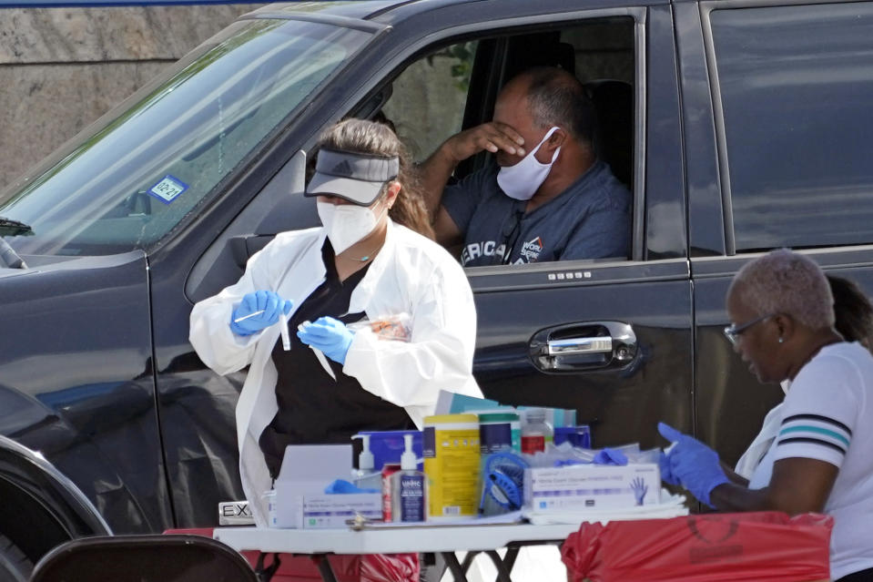 A patient reacts after a healthcare worker collected a sample at a United Memorial Medical Center COVID-19 testing site Thursday, July 16, 2020, in Houston. (AP Photo/David J. Phillip)