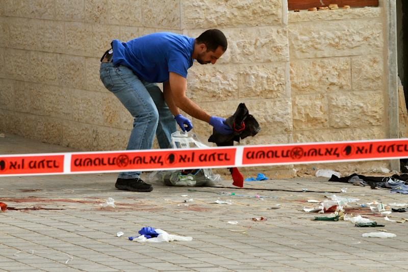 An Israeli policeman searches the site where two alleged Palestinian attackers were shot by Israeli police after attempting to board a bus carrying children and then stabbing an Israeli near Jerusalem on October 22, 2015 (AFP Photo/Gil Cohen Magen)