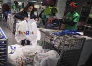 """A woman piles up her purchases at a Toys""""R""""Us store during their Black Friday Sale in New York November 28, 2013. REUTERS/Carlo Allegri"""