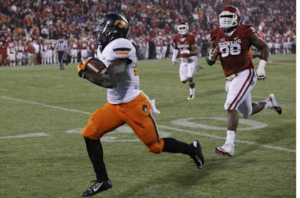 Oklahoma defensive tackle Chuka Ndulue (98) chases as Oklahoma State wide receiver Tyreek Hill, left, runs a punt return 91 yards for a touchdown in the fourth quarter of an NCAA college football game, tying the score and setting up an overtime, in Norman, Okla., Saturday, Dec. 6, 2014. Oklahoma State won 38-35 in overtime. (AP Photo/Sue Ogrocki)