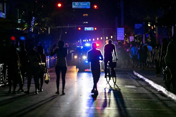 Beachers will leave Ocean Drive when police enforce a curfew for spring break at 8 pm on Friday, March 26, 2021 in Miami Beach, Florida.
