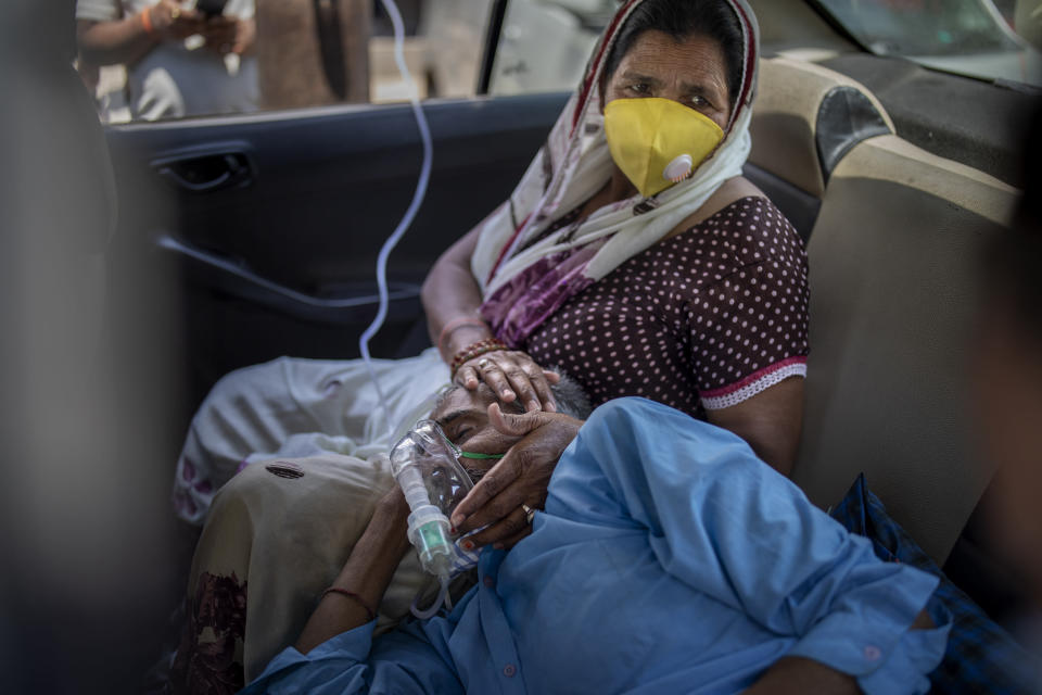 FILE - In this Saturday, April 24, 2021 file photo, a patient breathes with the help of oxygen provided by a gurdwara, a Sikh place of worship, inside a car in New Delhi, India. India's medical oxygen shortage has become so dire that a gurdwara began offering free breathing sessions with shared tanks to COVID-19 patients waiting for a hospital bed. (AP Photo/Altaf Qadri)
