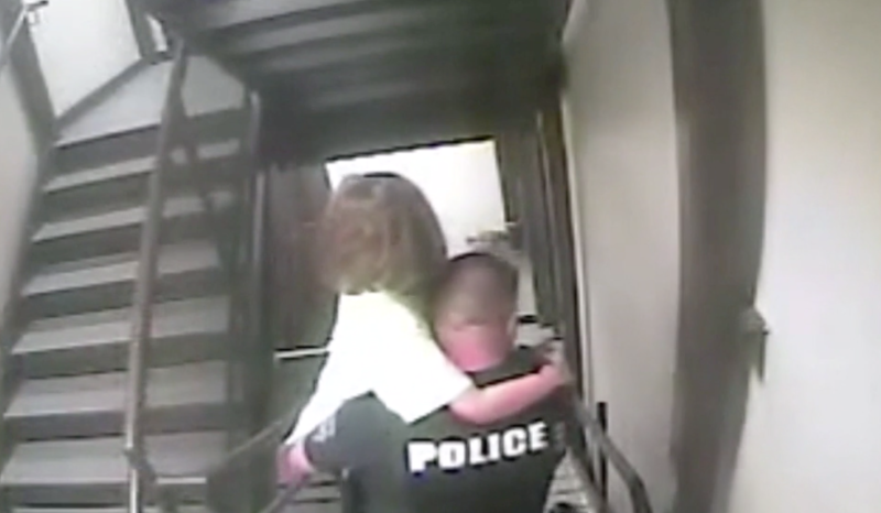 The young girl is carried out of the hotel by a police officer.