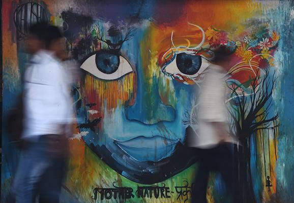 Indian officegoers walk past a wall displaying a mural in Mumbai on April 3, 2017. Graffiti featuring as social awareness messages, civic causes, religious figures, politicians, as well as daily life scenes cover the walls of certain streets of Mumbai. Written in English, Hindi or Marathi, these messages are of late being used for educational purposes than merely contributing to embellish the country's financial capital.