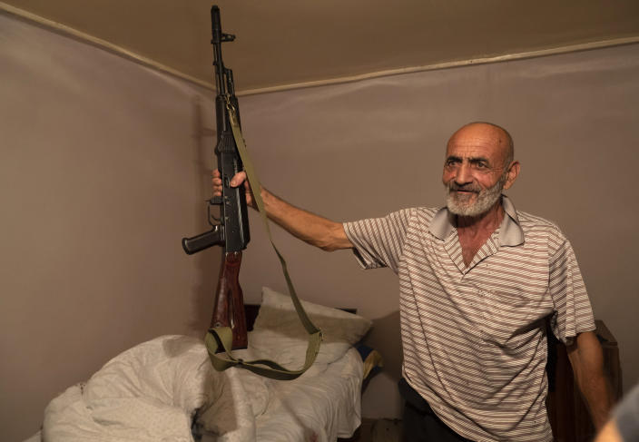 Local resident, Yury Ovanisyan holds a Kalashnikov guns that he received from a recruitment office in the town of Martuni, the separatist region of Nagorno-Karabakh, Wednesday, Oct. 14, 2020. The conflict between Armenia and Azerbaijan is escalating, with both sides exchanging accusations and claims of attacks over the separatist territory of Nagorno-Karabakh. Heavy fighting is in a third week despite a cease-fire deal. (AP Photo)