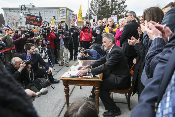 FILE - In this April 11, 2018 file photo, Vermont Gov. Phil Scott finishes signing a gun restrictions bill on the steps of the Statehouse in Montpelier, Vt. Scott faces a challenge by Springfield businessman Keith Stern in the Aug. 14, 2018, Republican primary. (AP Photo/Cheryl Senter, File)