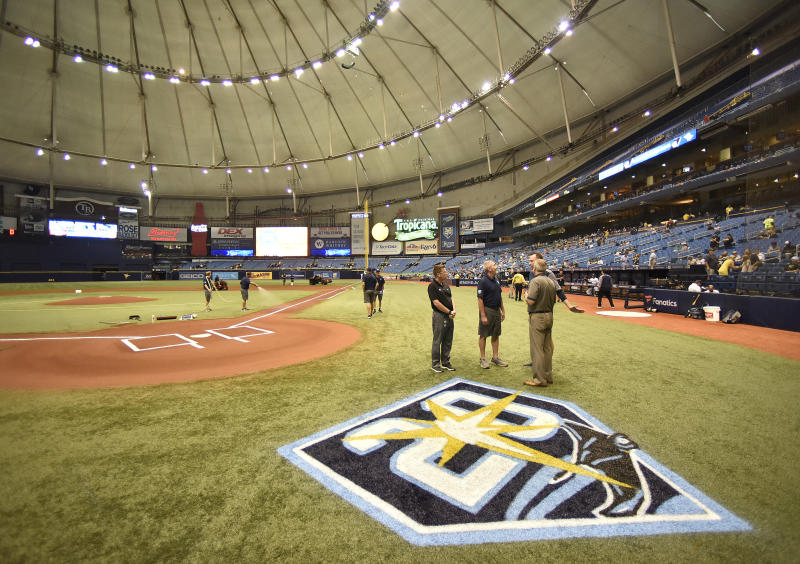 Tampa Bay Rays officials and grounds crew talk under emergency lightning after lightning strikes knocked out power inside Tropicana Field before the start of a game with the New York Yankees Monday, Sept. 24, 2018, in St. Petersburg, Fla. (AP Photo/Steve Nesius)