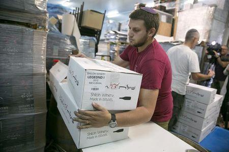 A worker carries boxes containing wine bottles for export, north of Ramallah