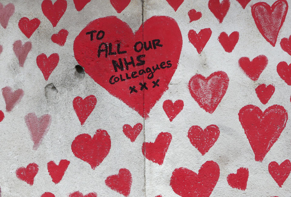 A close up of the hearts on the 'The National COVID Memorial Wall' on the south bank of the Thames in front of St. Thomas' hospital and opposite the House of Parliament in London, Sunday April 4, 2021. Hearts are being drawn onto the wall in memory of the many thousands of people who have died in the UK from coronavirus, with organizers hoping to reach their target of 150,000 hearts by the middle of next week. (AP Photo/Tony Hicks)